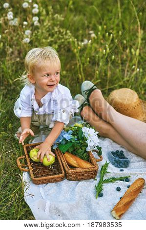 Cheerful baby in bright clothes with apples in the open air