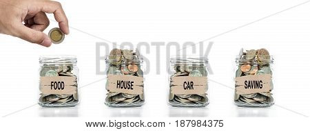 Hand putting coin in glass jar. Allocate money for foods, house, car and savings. Save money concept