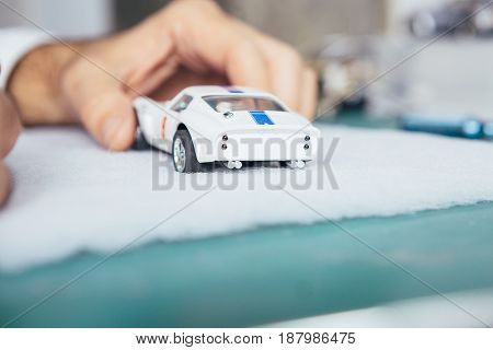 Unrecognizable person holding handcrafted miniature auto in a workshop.