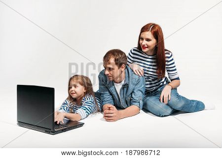 Happy funny family Father, mother and child lying on the floor with laptop on white background isolated