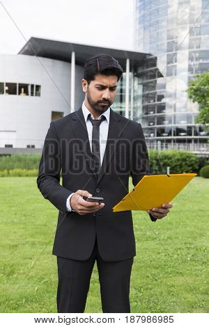 Arabic businessman or worker in black suit with tie and shirt standing in front of an office building holding yellow folder or document case and a cellphone in hands on green grass in summer day.