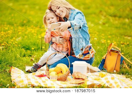 Portrait of happy family of two people. Blonde mum and daughter enjoying picnic in park.Selective focus on cellphone.