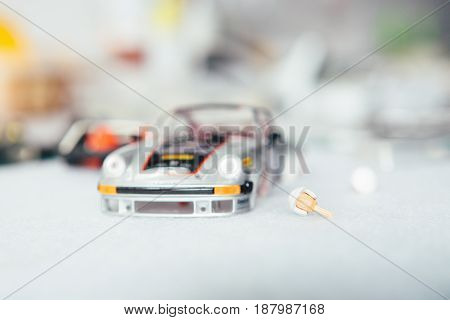 Slot car under construction and head of toy driver on a table in workshop.