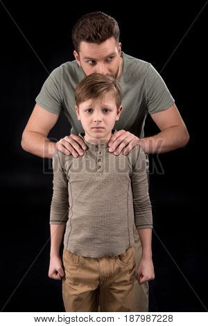 Father Putting Hands On Shoulders Of Scared Little Son, Family Problems Concept