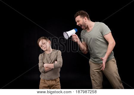 Father With Megaphone Screaming At Little Son Standing With Crossed Arms, Family Problems Concept