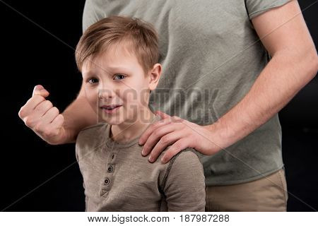 Cropped shot of father threatening and gesturing to scared little son family problems concept
