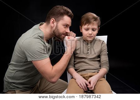 Angry Father Threatening And Gesturing To Scared Little Son Sitting On Chair, Family Problems Concep