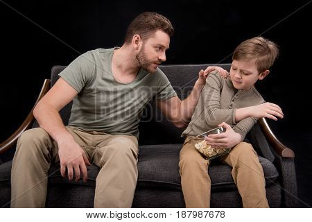 Angry Father Looking At Scared Little Son Sitting On Sofa With Popcorn In Bowl, Family Problems Conc
