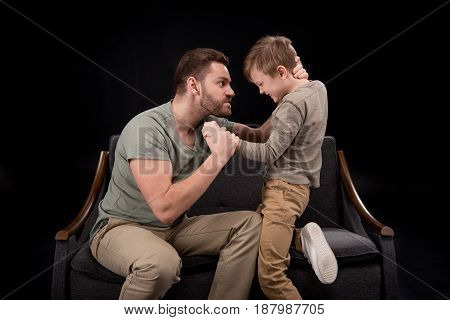 Angry Father Threatening To Scared Little Boy Isolated On Black, Family Problems Concept