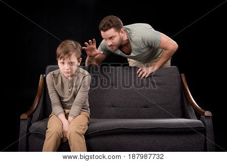 Angry Father Gesturing To Scared Little Son Sitting On Sofa, Family Problems Concept