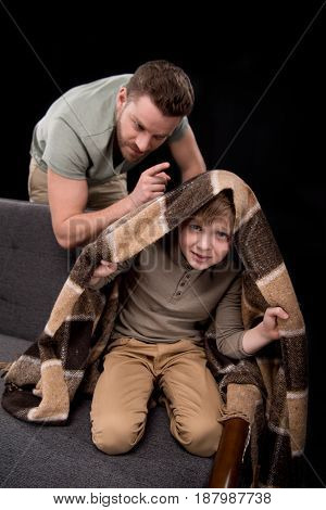 Angry Father Threatening To Scared Little Boy Hiding Under Blanket On Sofa, Family Problems Concept