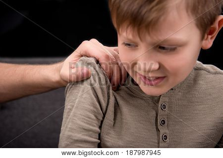 Close-up partial view of father threatening to scared little boy family problems concept