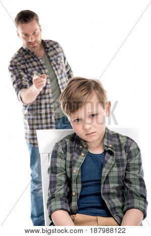 Father Gesturing To Scared Little Boy Sitting On Stool, Family Problems Concept