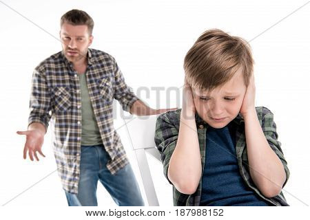 Father Gesturing And Quarreling With Scared Little Boy Closing Ears, Family Problems Concept