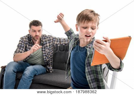 Father Gesturing And Looking At Emotional Little Son Using Digital Tablet, Family Problems Concept