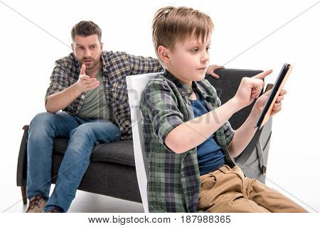 Father Talking With Little Son Sitting On Chair And Using Digital Tablet, Family Problems Concept