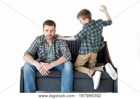 Father And Son Sitting On Sofa And Quarreling, Family Problems Concept
