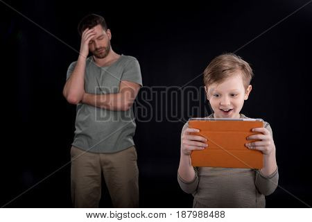 Upset Father Standing Behind Excited Son Using Digital Tablet, Family Problems Concept