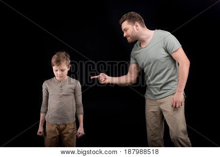 Angry Father Threatening And Gesturing To Scared Little Son, Family Problems Concept