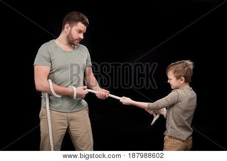 Father And Son Pulling Rope Isolated On Black, Family Problems Concept