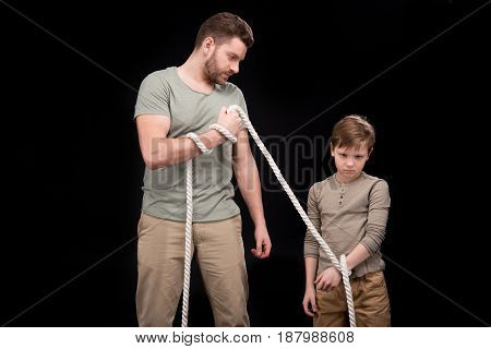 Father With Rope Tied Upset Little Son, Family Problems Concept