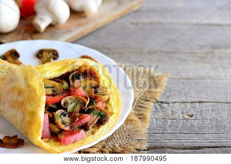 Stuffed egg omelette. Mushrooms omelette with tomatoes and dill on a plate and on a wooden background with copy space for text. Quick and easy breakfast omelette. Rustic style