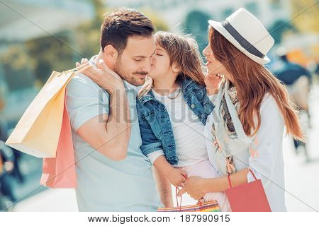 Happy family with shopping bags in the city.Sale consumerism and family concept.