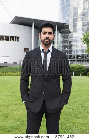 Arabic eastern indian serious businessman or worker in black suit with tie and shirt with beard standing in front of an office building with hands in pockets on green grass in summer day.