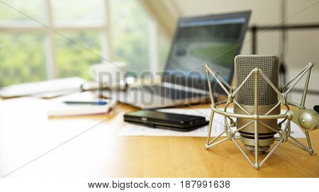 workspace for journalism with condenser microphone laptop cellphone and notepad on a desktop at the window short panoramic banner for website headerwith blurred background copy space