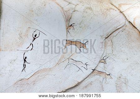 Concept painted on a rock, ancient people hunt animal buffalo with a spear
