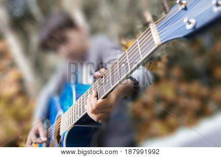 Boy playing a blue guitar. Outdoors shot