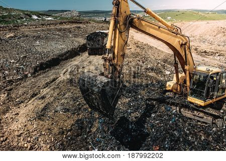 Industrial Heavy Duty Machinery, Excavator Digging Hole And Loading Garbage Into Dumper Trucks
