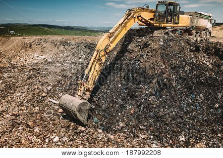 Industrial Machinery Excavating Garbage. Close Up Of Heavy Duty Excavator Using Scoop And Working