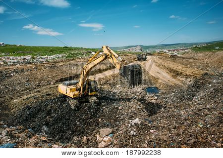 Excavator Loader, Bulldozer Working In Garbage Dump. Recycling And Resolving Environmental Issues