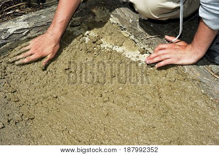 Dirty muddy hands prepare the soil of a vegetable garden