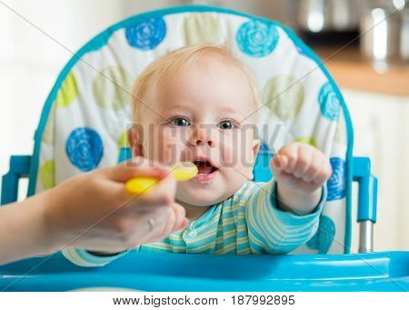 family and nutrition concept - mother spoon feeding little baby son sitting in highchair at home