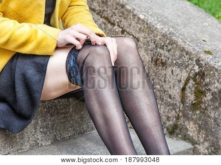 young woman adjusting her stocking sitting on the stairs outdoor closeup