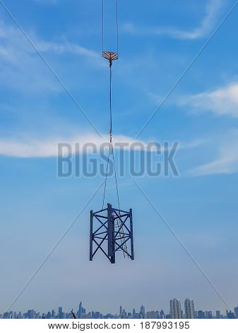 Mast crane was raised in the air at the top of the tower white blue sky background.