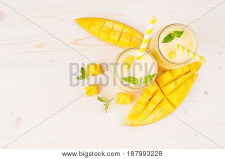 Decorative border of yellow mango fruit smoothie in glass jars with straw mint leaves mango slices top view. White wooden board background copy space.