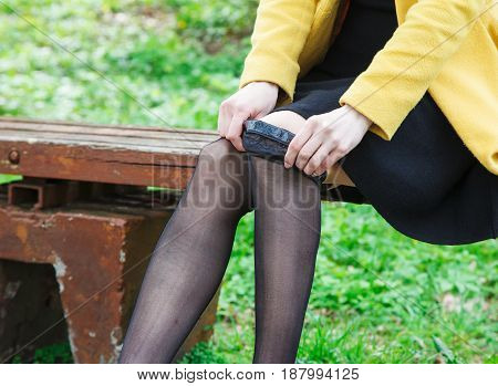 young woman adjusting her stocking sitting on the bench outdoor closeup