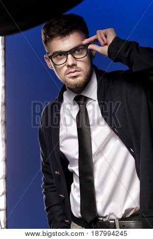 Fashion Portrait of a handsome young man with glasses and a white shirt on a blue background