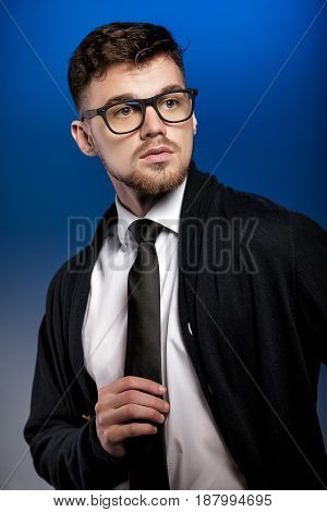 Portrait of a handsome young man with glasses and a white shirt on a blue background