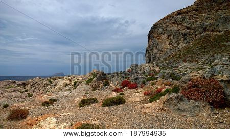 View of the island of Gramvousa, Crete (Greece) - boulders, stones, bushes of bright red color and the sea in the background