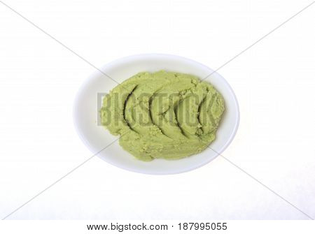 Bowl with wasabi isolated on white background