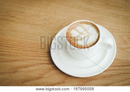 Cup of coffee on wood background retro style with copy space
