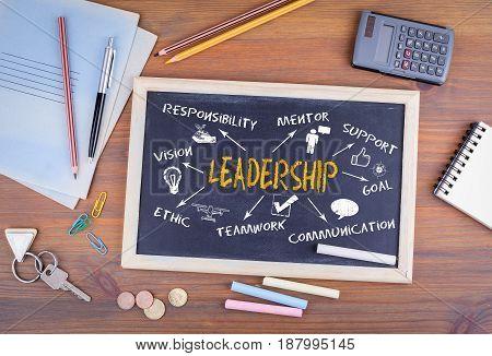 Leadership concept. Chalkboard on wooden office desk.