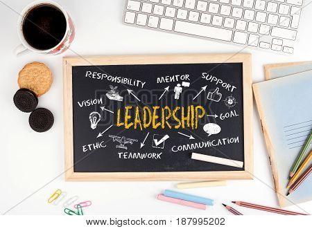 Leadership concept. Chalkboard on white office desk.