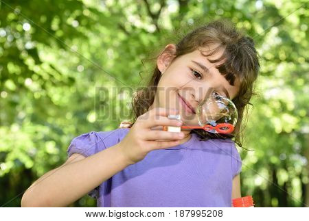Cute young girl playing with the soap bubble in the park