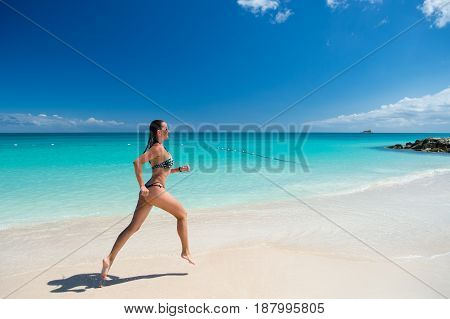 Young pretty sexy woman with beautiful body in swimsuit running in ocean water sunny day at tropicl beach wellness concept