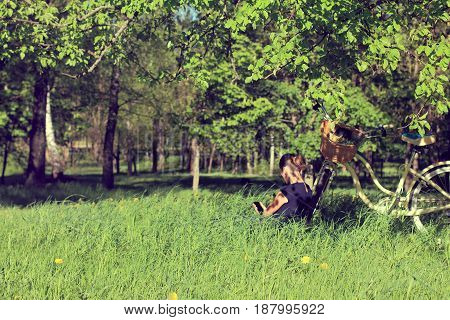green lawn with shady trees under which unrecognizable girl with a bicycle relaxing looking at smart-phone/ summer holiday in the fresh air